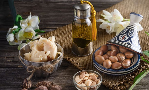 still-life-of-argan-oil-and-fruit-and-shea-butter-with-nuts-on-a-wooden-table-with-flowers.jpg